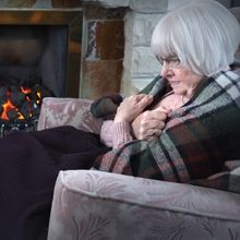 Elderly woman trying to keep warm by the fireside